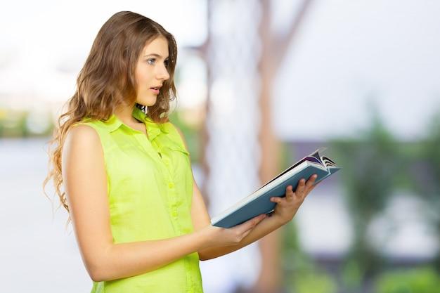 Retrato de un adolescente femenino alegre con un libro