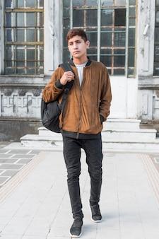 Retrato de un adolescente con la mano en el bolsillo que lleva la bolsa en el hombro caminando frente al edificio