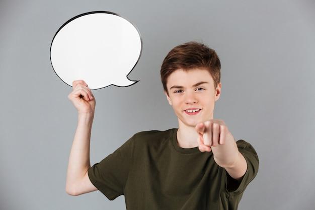 Retrato de un adolescente masculino sonriente con bocadillo en blanco y señalar con dedo