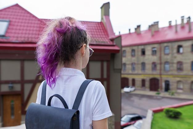 Retrato de una adolescente con mochila de pie hacia atrás mirando el edificio de la escuela. regreso a la escuela, regreso a la universidad, educación, aprendizaje, niños, concepto de adolescentes