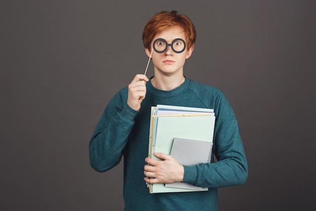 Retrato de adolescente pelirroja guapo divertido en suéter verde de moda con cuadernos en la mano, mirando con los ojos aparecidos a través de vasos de papel en el palo.