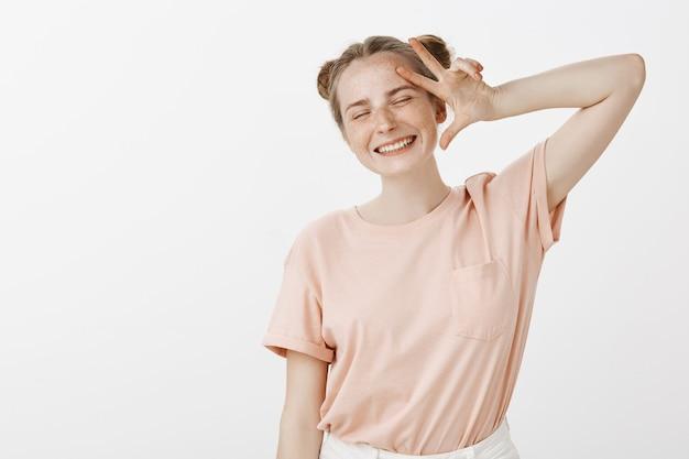 Retrato de una adolescente positiva posando contra la pared blanca