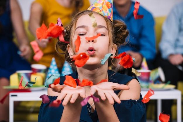 Retrato de una adolescente que sopla confeti en su cumpleaños