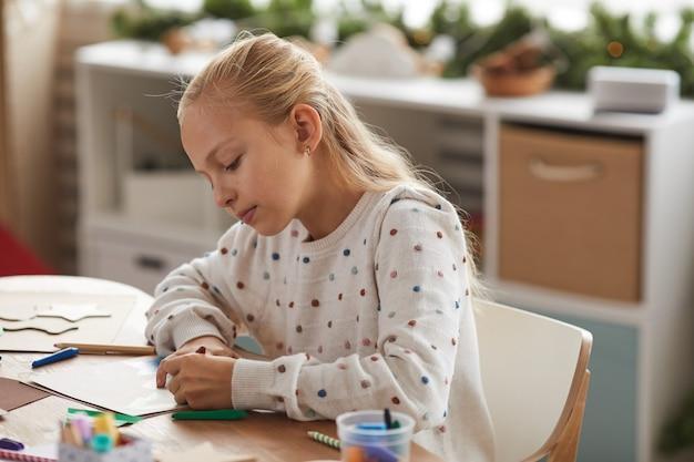 Retrato de una adolescente rubia dibujando en casa o disfrutando de la clase de arte y artesanía en la escuela