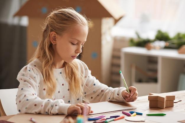 Retrato de una adolescente rubia dibujando o haciendo los deberes mientras está sentado en el escritorio en el interior de una casa, espacio de copia