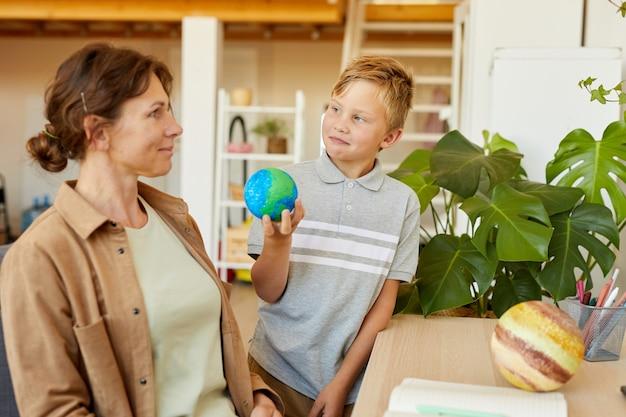 Retrato de adolescente rubia sosteniendo el modelo de planeta mientras estudiaba en casa con la madre, espacio de copia