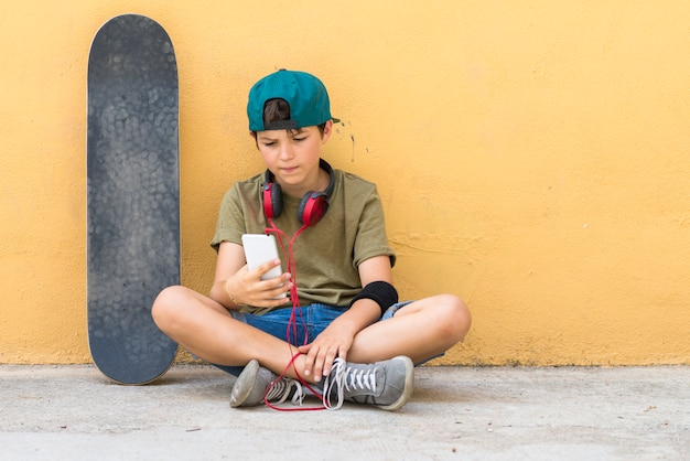 Retrato de un adolescente sentado en el suelo en una calle charlando (skateboard en la pared)