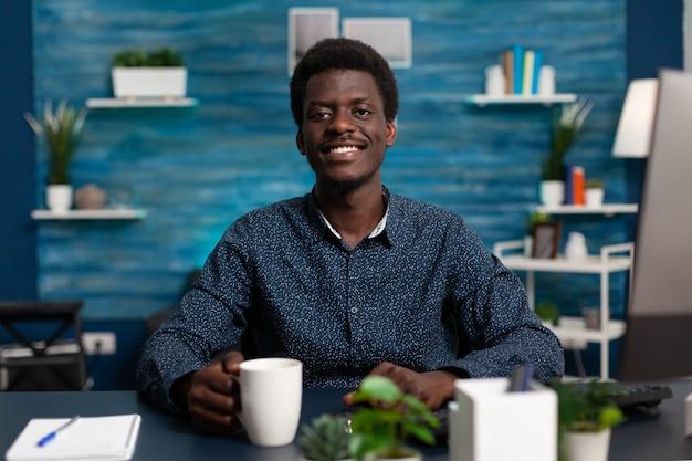 Retrato de adolescente sonriente sosteniendo una taza de café mientras estudia en una lección de administración usando una clase universitaria en línea durante el bloqueo del coronavirus. hombre negro trabajando lejos de casa