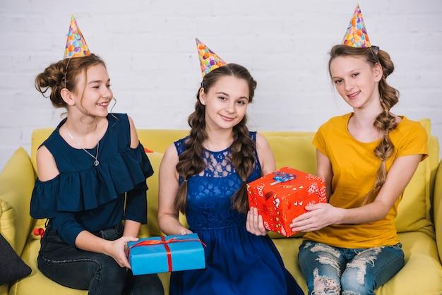 Retrato de adolescentes felices que se sientan en el sofá amarillo con sus amigos que llevan a cabo presentes
