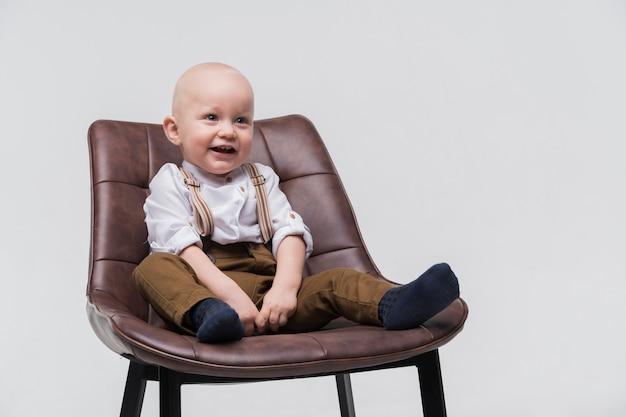 Retrato de adorable bebé sentado en una silla