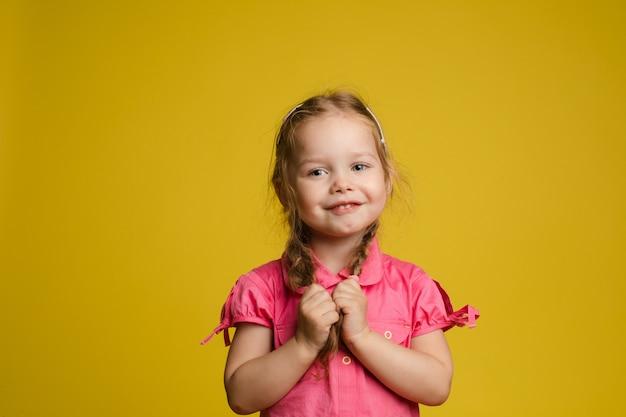 Retrato de adorable niña linda niña sosteniendo el pelo posando mirando a la cámara tiro medio