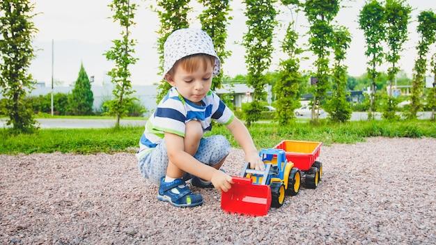 Retrato de adorable niño pequeño de 3 años jugando con camión de juguete con remolque en el patio de recreo en el parque