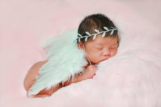 Retrato adorable del pequeño bebé recién nacido con traje de ángel y alas blancas, durmiendo sobre una tela suave y esponjosa