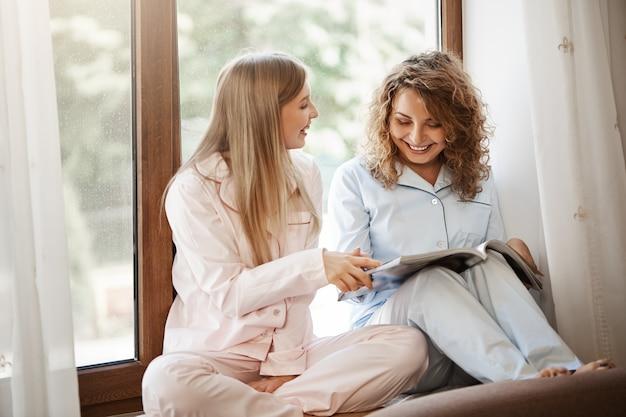 Retrato de adorables amigos sentados en el alféizar de la ventana en pijama, leyendo una revista