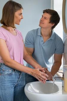 Retrato de adorables padres lavándose las manos