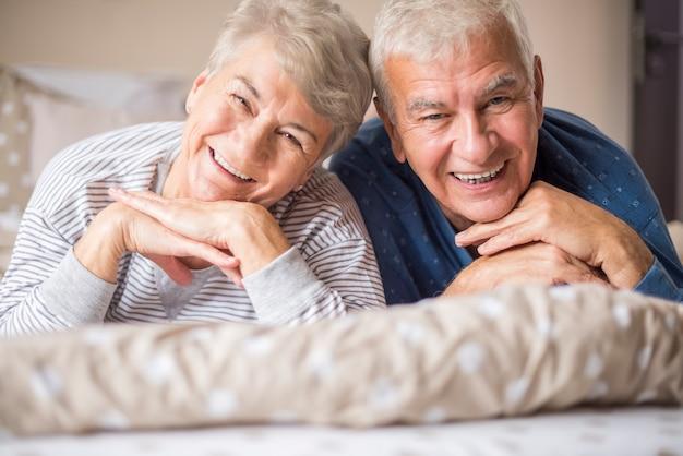 Retrato de adultos mayores alegres en el dormitorio