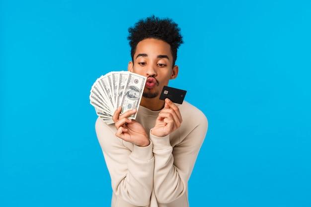Retrato afroamericano adicto y complacido tipo afroamericano mirando dinero precioso y tarjeta de crédito, como retirar dinero en efectivo en la temporada de rebajas de vacaciones de invierno, besarlos, azul