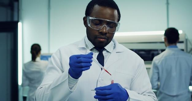Retrato del afroamericano guapo trabajador de laboratorio masculino haciendo un análisis de sangre en el tubo de vidrio en las manos. de cerca.