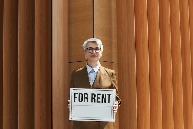 Retrato de agente inmobiliario maduro en anteojos sosteniendo cartel en alquiler
