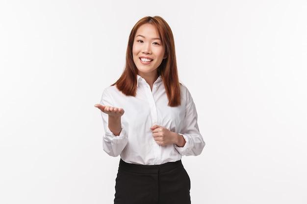 Retrato de agradable empresaria asiática elegante, dama de oficina en ropa formal, apuntando con la mano a la cámara y sonriendo, hablando con un socio comercial, persona de reunión,