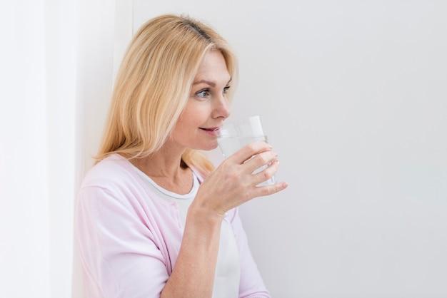 Retrato de agua potable encantadora mujer senior