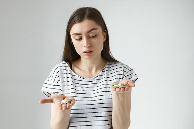 Retrato aislado de dudosa joven europea pensativa posando con las manos abiertas frente a ella, sosteniendo un montón de píldoras multicolores en sus palmas, eligiendo entre antibióticos y vitaminas