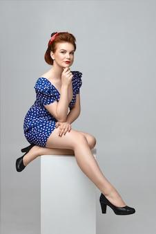 Retrato aislado de la hermosa y misteriosa modelo de mujer joven con hermosas piernas y cuerpo curvilíneo relajándose en el interior, sentado sobre una cosa blanca con las piernas cruzadas, tocando la barbilla
