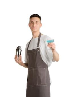 Retrato aislado de un joven barista caucásico o camarero en delantal marrón sonriendo