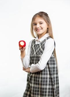 Retrato aislado de niña feliz en uniforme escolar con manzana roja