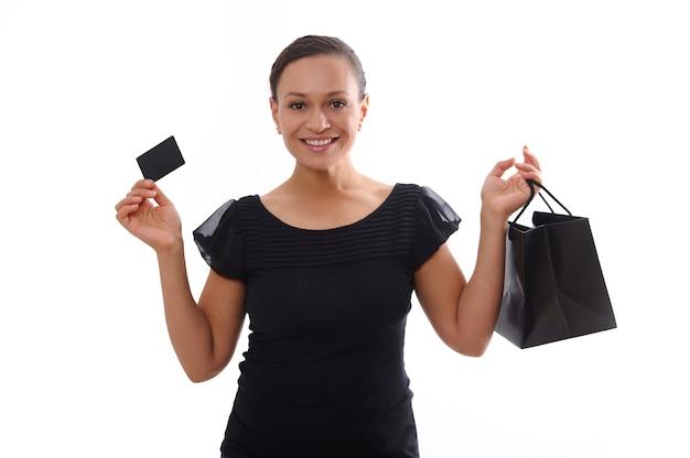 Retrato aislado sobre fondo blanco con espacio de copia de una atractiva mujer sonriente vestida de negro y sosteniendo una tarjeta de crédito de descuento y una bolsa de compras, mirando a la cámara. concepto de viernes negro