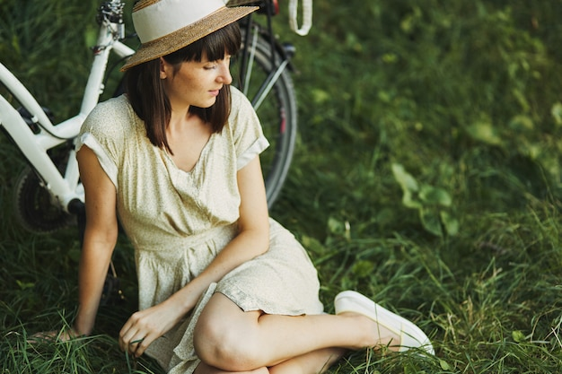 Retrato al aire libre de la atractiva joven morena con un sombrero en una bicicleta.