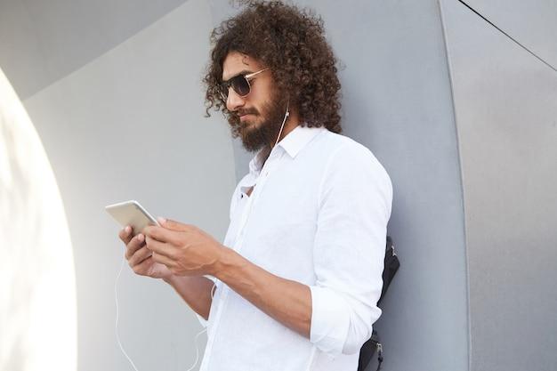 Retrato al aire libre de atractivo hombre rizado de pie sobre una pared gris, leyendo noticias en la tableta mientras espera a alguien, con ropa casual y gafas