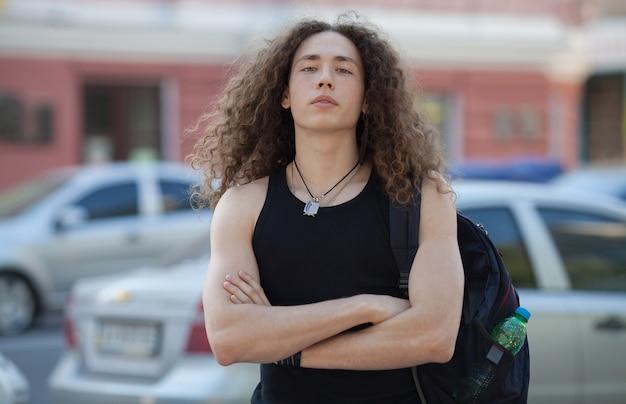 Retrato al aire libre de la calle moderna joven a pie. hombre con cabello largo y rizado.