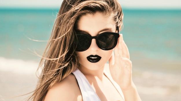 Retrato al aire libre cerca de una linda chica en gafas de sol y labios pintados oscuros disfrutando de su tiempo en la playa