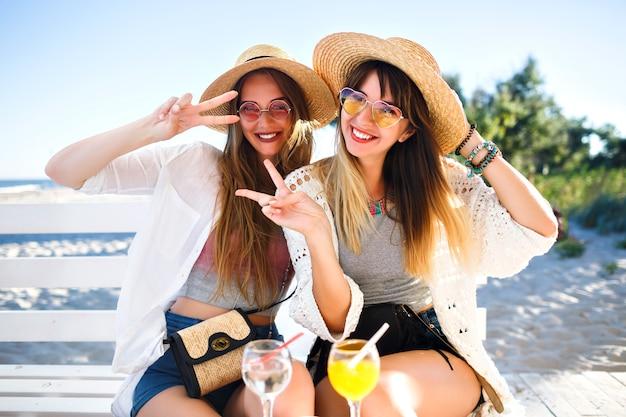 Retrato al aire libre de las chicas hipster divertidas felices de la compañía volviéndose locas en el café de la playa, bebiendo deliciosos cócteles riendo y sonriendo, trajes de verano boho brillante vintage, relaciones y diversión.