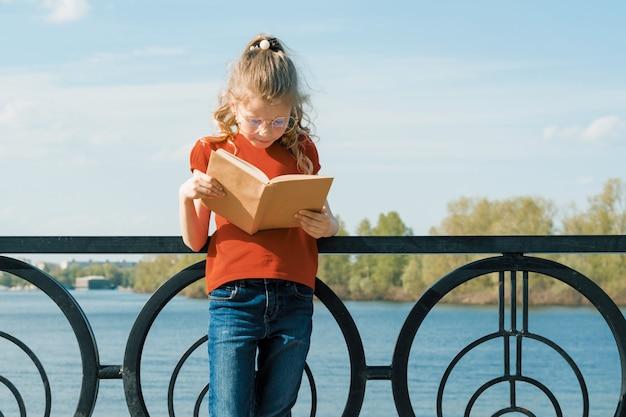 Retrato al aire libre de colegiala con libro, niña