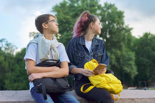 Retrato al aire libre de dos adolescentes hablando con teléfono inteligente