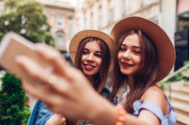 Retrato al aire libre de dos mujeres hermosas jovenes que toman el selfie usando el teléfono. chicas divirtiéndose en la ciudad. mejores amigos
