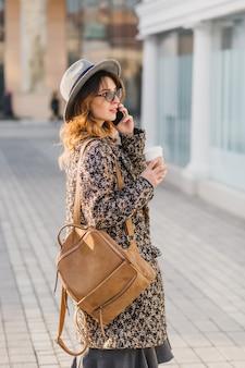 Retrato al aire libre de elegante señorita con mochila marrón con abrigo y sombrero. mujer atractiva con cabello rizado hablando por teléfono mientras toma café en la calle y espera amigos.