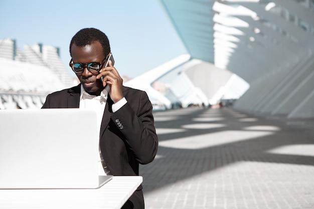 Retrato al aire libre de un exitoso empresario africano confiado o trabajador corporativo con traje negro y elegantes tonos que tiene una conversación telefónica y trabaja de forma remota en la computadora portátil en el café urbano