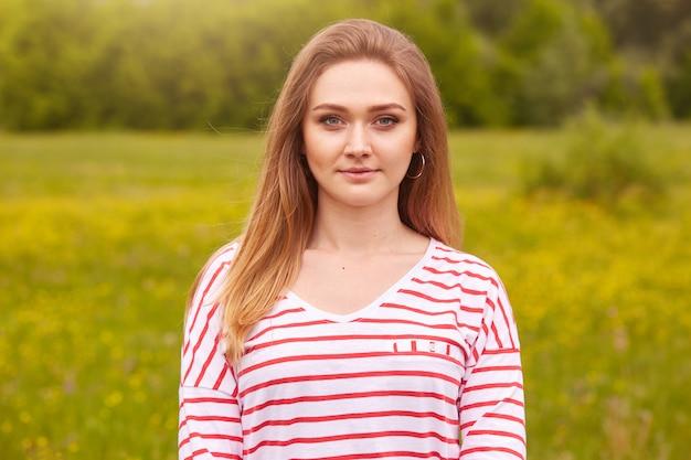 Retrato al aire libre de feliz niña sonriente con el pelo largo y liso en camisa blanca con rayas rojas posando en el prado de verano, tiene expresiones faciales tranquilas y agradables, siendo fotografiado por un amigo.