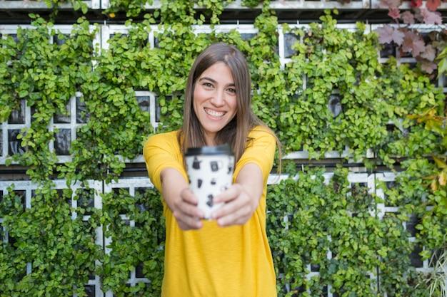 Retrato al aire libre de una hermosa joven sosteniendo una taza de café y sonriendo. vistiendo una camisa casual amarilla sobre fondo verde. estilo de vida y diversión.