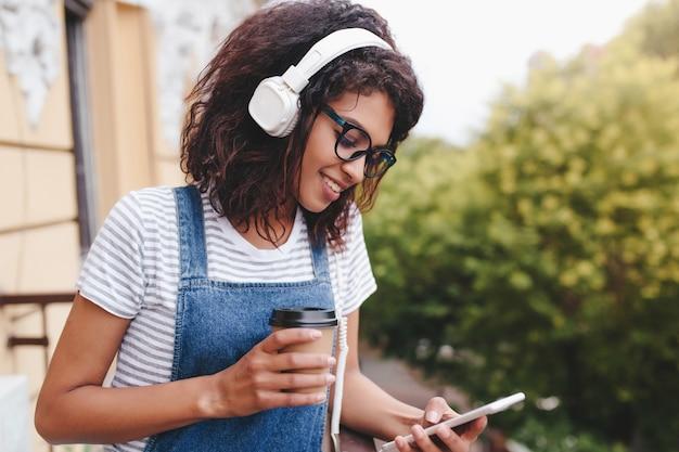 Retrato al aire libre de hermosa mujer joven en camisa a rayas mirando hacia la pantalla del teléfono y sosteniendo una taza de café