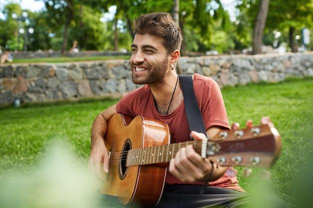 Retrato al aire libre de hombre guapo sonriendo, sentado en el césped en el parque y tocando la guitarra