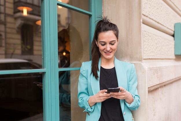 Retrato al aire libre de joven blogger feliz mujer con teléfono móvil. fondo de ventanas de vidrio. usando ropa casual. diversión y estilo de vida.