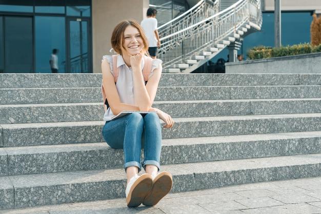 Retrato al aire libre de joven hermosa niña estudiante sonriente
