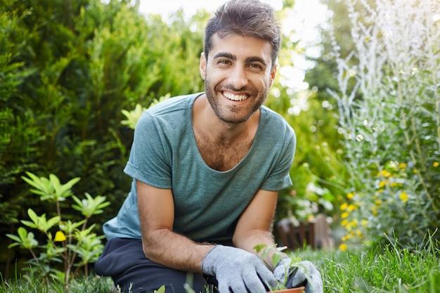 Retrato al aire libre de joven jardinero masculino caucásico barbudo atractivo en camiseta azul sonriendo en la cámara, plantando semillas en el jardín, regando plantas de cerca.