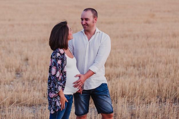 Retrato al aire libre de una joven pareja embarazada caminando por un campo amarillo. estilo de vida familiar al aire libre.