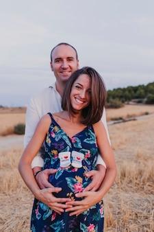 Retrato al aire libre de una joven pareja embarazada en un campo amarillo. estilo de vida familiar al aire libre. sosteniendo calcetines con el mensaje i love mum, i love dad