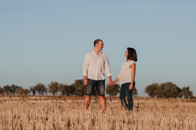 Retrato al aire libre de una joven pareja joven embarazada en un campo amarillo. estilo de vida familiar al aire libre.